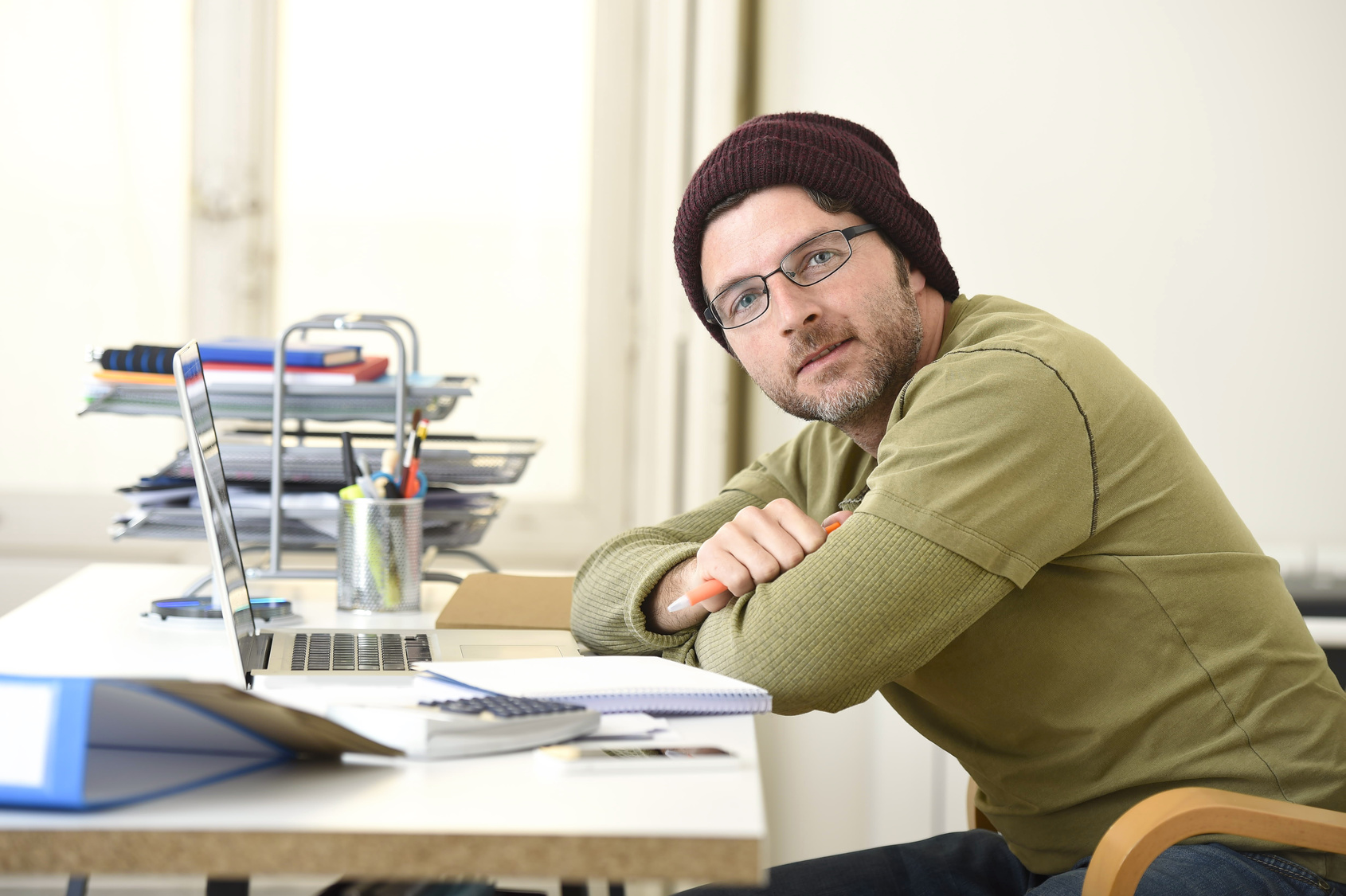 corporate young attractive hipster businessman working at home office as freelancer in casual beanie leaning on computer desk smiling happy and confident  in freestyle business