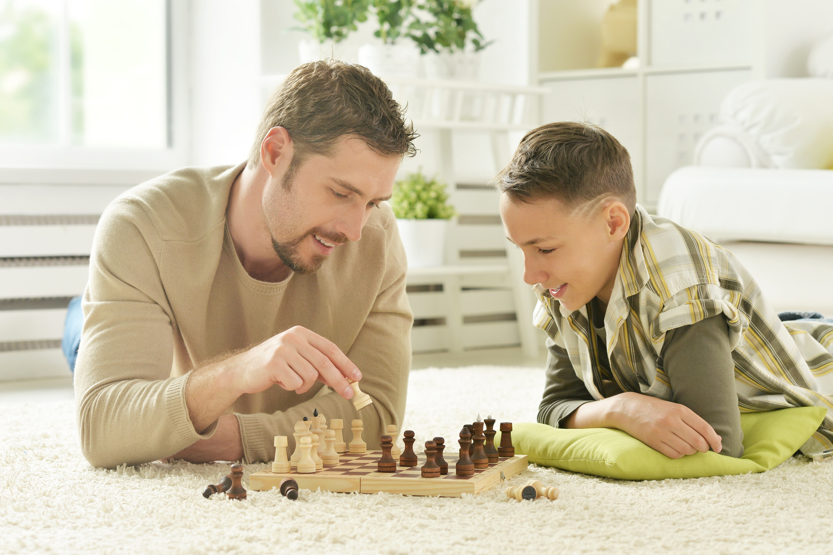 portrait of happy father and son playing chess